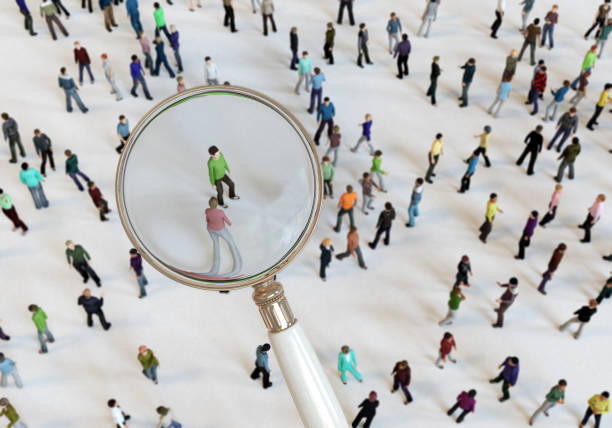 Magnifying Glass On Crowd of People stock photo