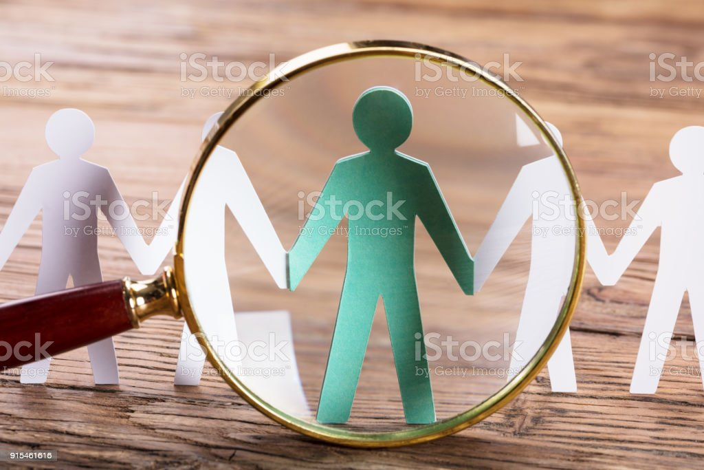 Magnifying Glass On Cut-out Figures stock photo