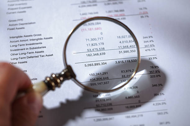 Magnifying glass on financial report Businessman holding a magnifying glass on a financial report concept for finance, balance sheet, tax or accounting bank statement stock pictures, royalty-free photos & images