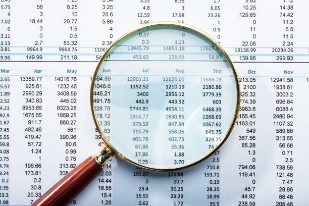 magnifying glass on financial report - bills and taxes stock pictures, royalty-free photos & images