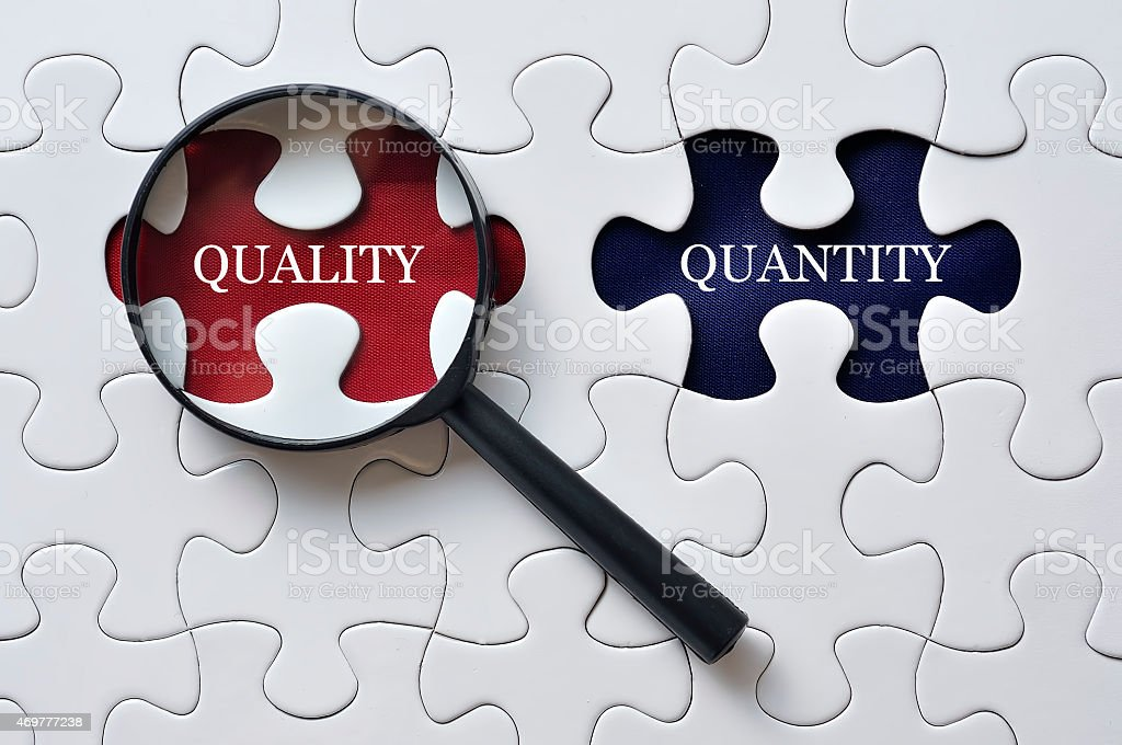 Magnifying Glass On Missing Puzzle with 'QUALITY/QUANTITY' Word, Antonym Concept stock photo