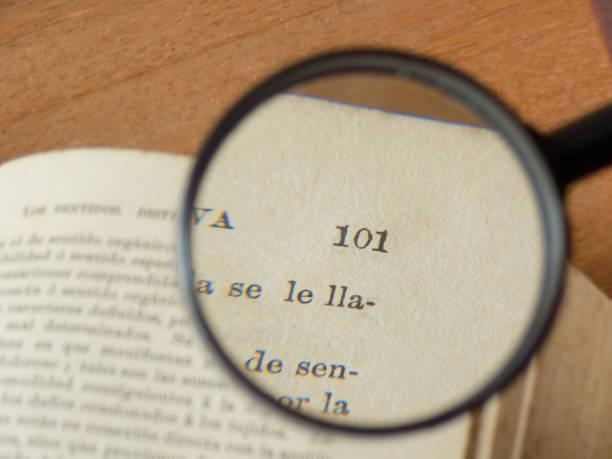 Magnifying Glass on page La composición muestra una lupa usada en la lectura de una página. libro stock pictures, royalty-free photos & images