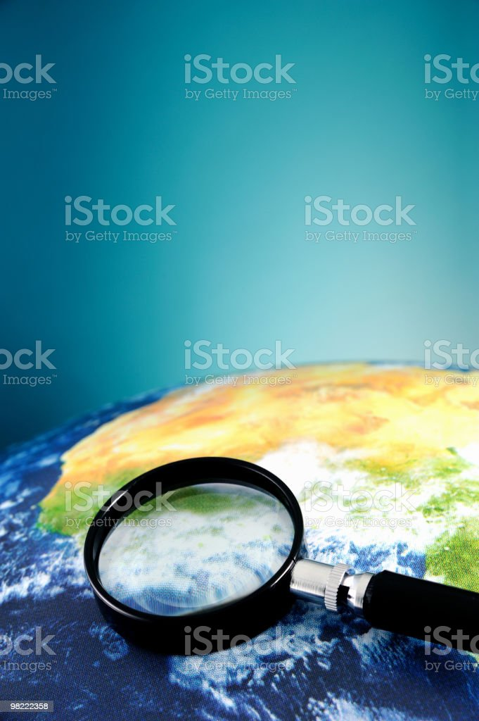 Magnifying glass on planet Earth royalty-free stock photo