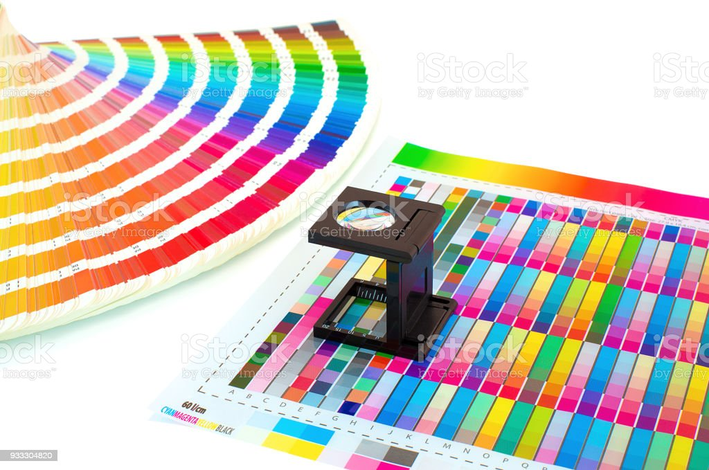 Magnifying glass on printed color swatch isolated on white. Color management in printing process with magnifying glass and paint guide.  Color selection Pre-Press concept. Loupe and a ink sampler. stock photo