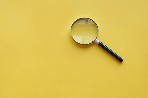 Magnifying glass on the orange background stock photo