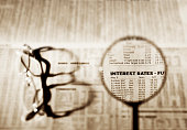 Loupe  and reading glasses on financial newspaper