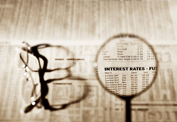 magnifying glass on the words interest rates on newspaper - rates stock photos and pictures