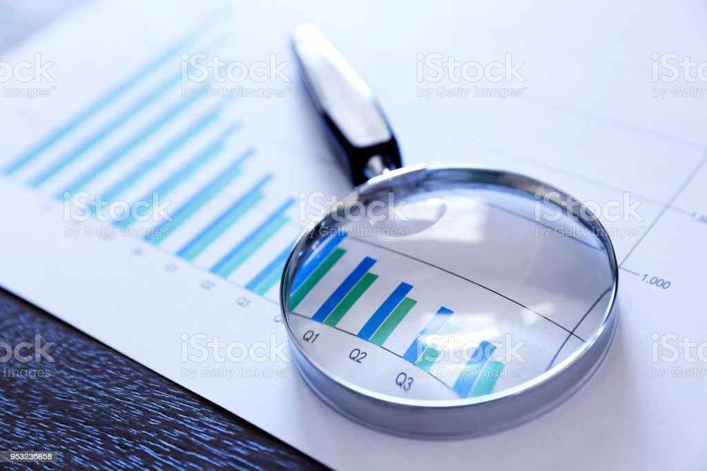 A magnifying glass rests on top of a bar graph that shows declining...