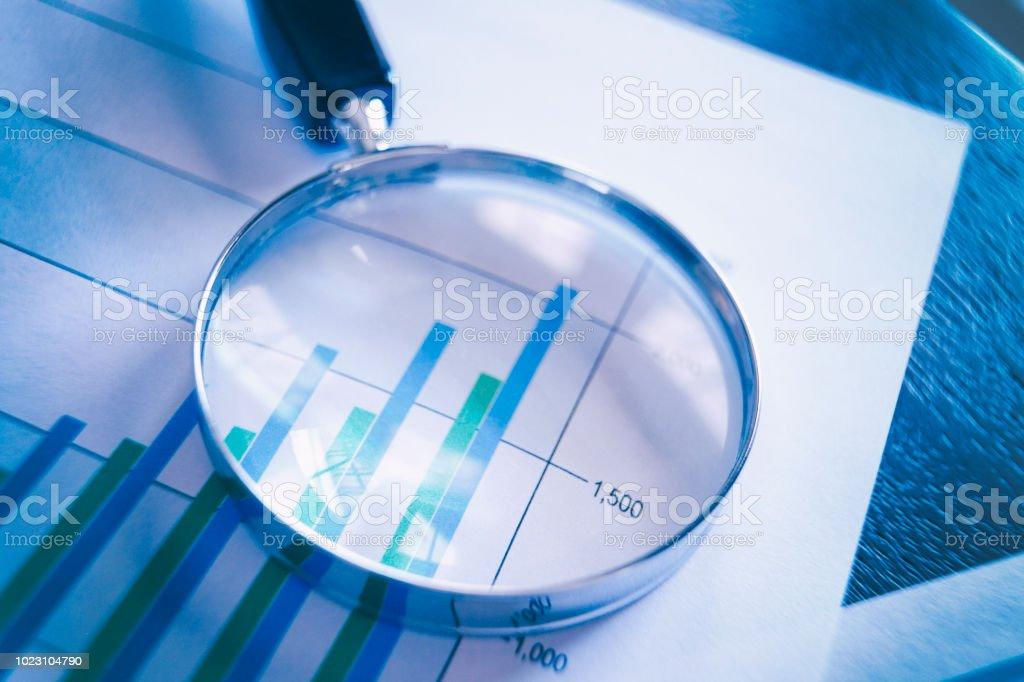 Magnifying Glass On Top Of Bar Chart Showing Increasing Performance stock photo