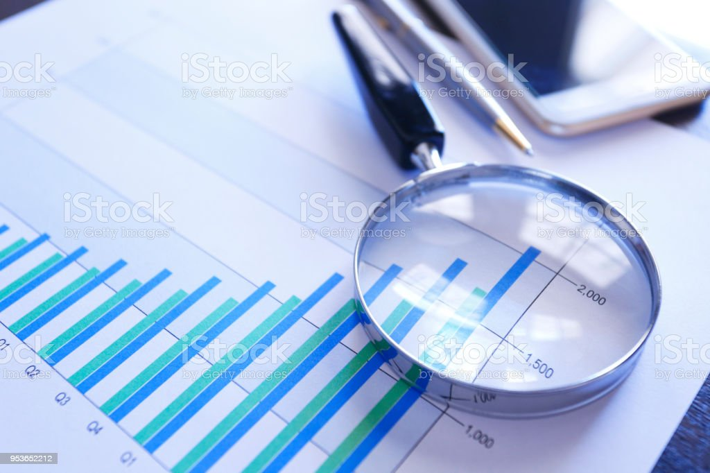 A magnifying glass rests on top of a bar graph that shows increasing...