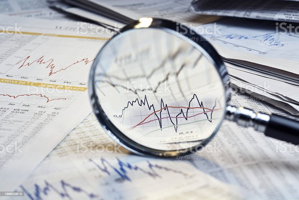 Magnifying glass on top of financial market info stock photo