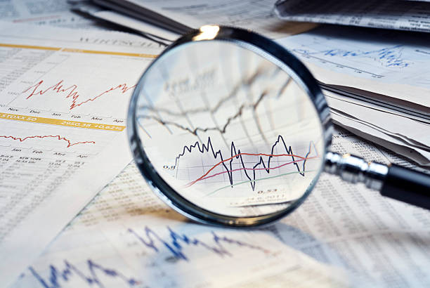 Magnifying glass on top of financial market info Magnifying glass and newspapers with exchange rate tables and diagrams. scrutiny stock pictures, royalty-free photos & images