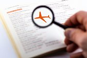 Magnifying glass on travel guide with airplane