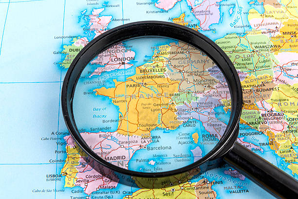 Magnifying glass over a map focusing on France stock photo