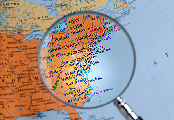 Magnifying glass over a map of East Coast close up of East Coast thru a magnifying glass eastern usa stock pictures, royalty-free photos & images