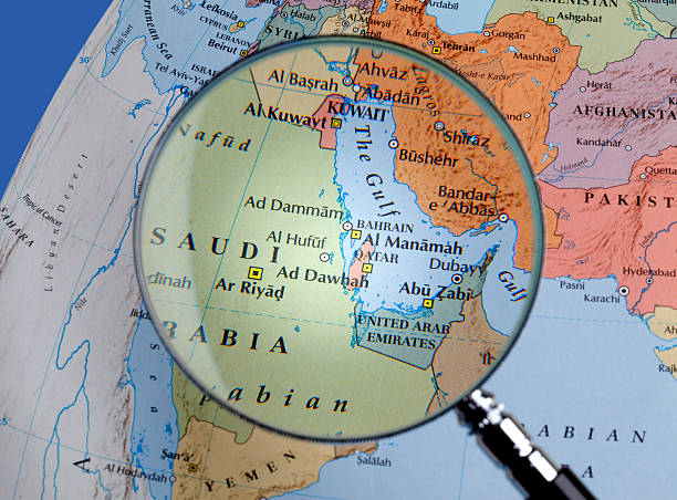 magnifying glass over a map of middle east - saudi arabia map stock photos and pictures