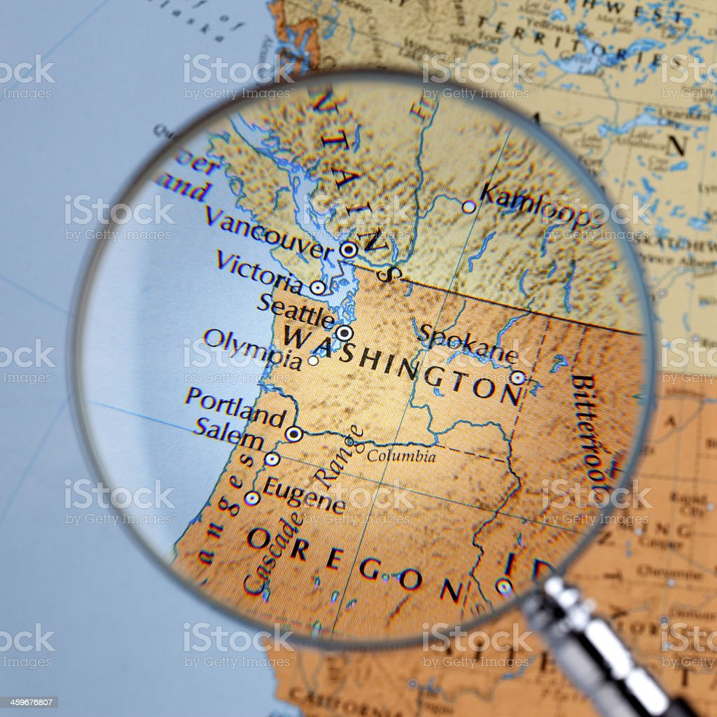 Magnifying glass over a map of WASHINGTON stock photo