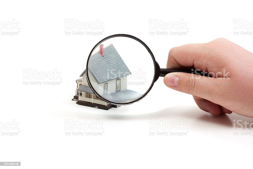 Magnifying glass over a toy house royalty-free stock photo