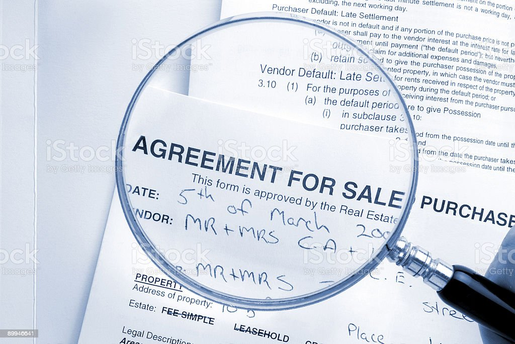 Magnifying Glass Over Real Estate Contract stock photo