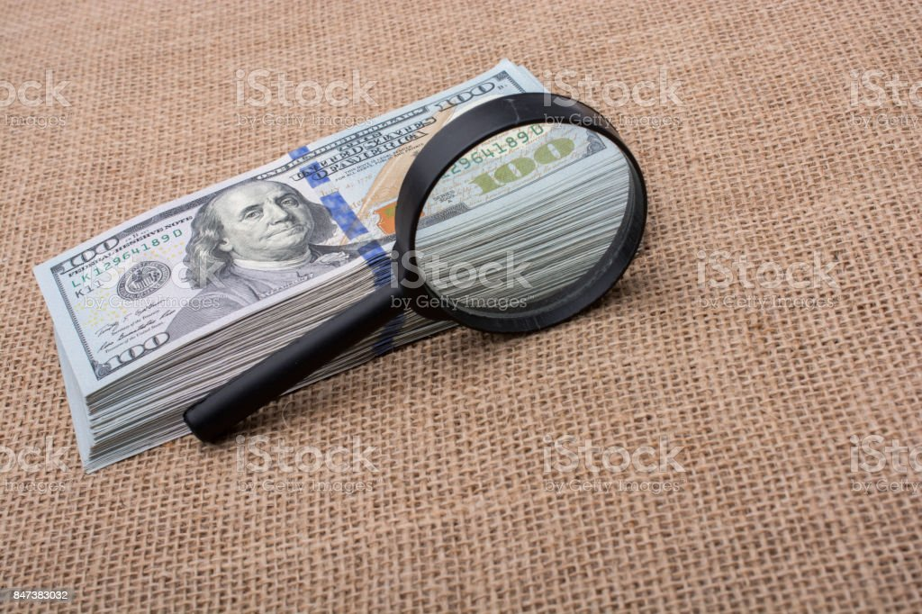 Magnifying glass over the banknote bundle of US dollar stock photo