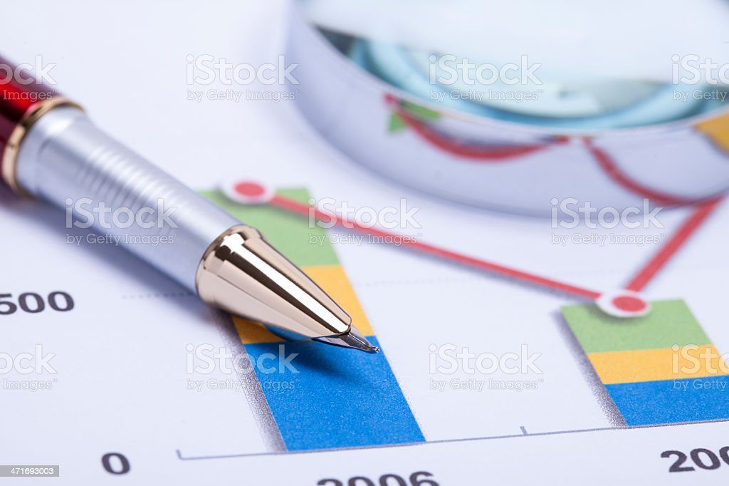 Magnifying glass, pen and financial report stock photo