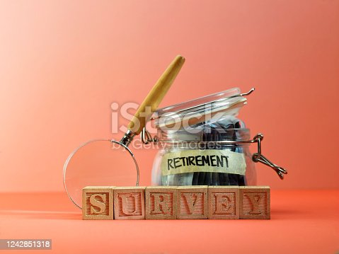 Wooden Blocks with the text: Survey and retirement saving jar with magnifying glass