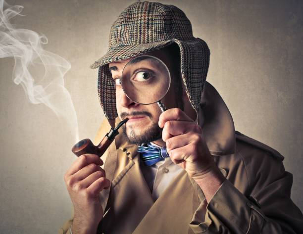 Magnifying glass A detective with a magnifying glass in his hand detective stock pictures, royalty-free photos & images