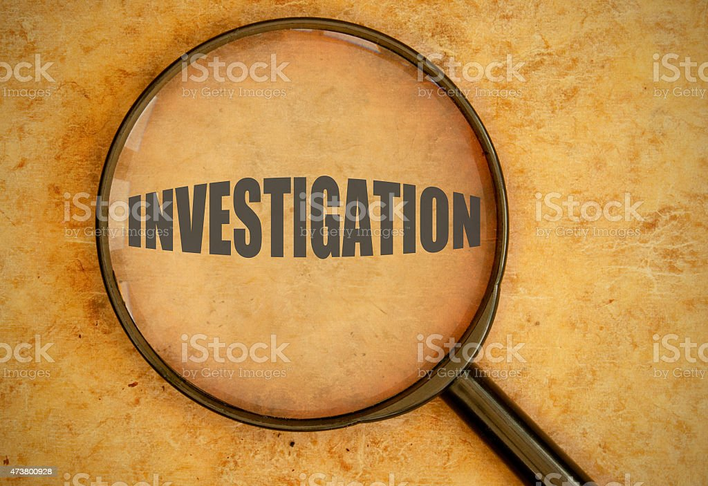 A magnifying glass revealing the word INVESTIGATION  stock photo