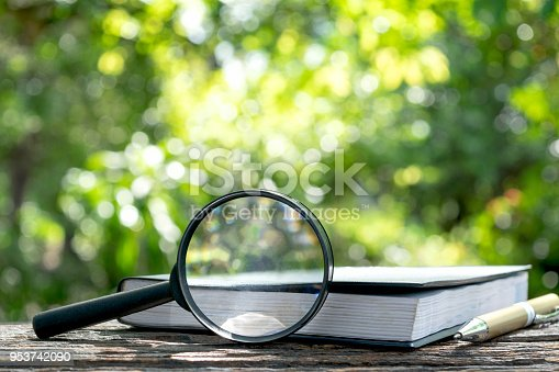 istock magnifying glass with a book on wooden  in nature background concept. 953742090