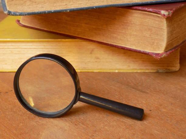 Magnifying Glass with books II En esta toma se intenta dar la impresión de libros recientemente usados, pues se muestran apilados en desorden. libro stock pictures, royalty-free photos & images