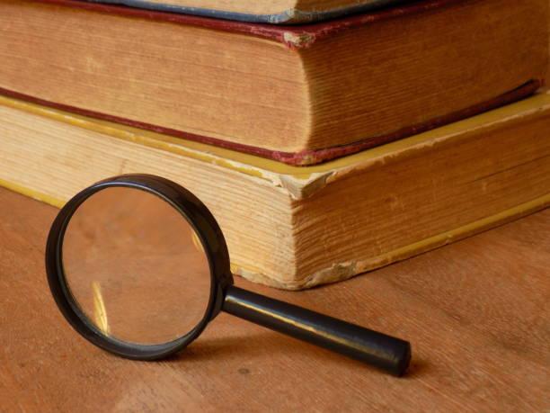 Magnifying Glass with books III En esta toma la composición muestra el vértice de los libros en dirección a la cámara y la lupa sostenida en posición vertical. libro stock pictures, royalty-free photos & images