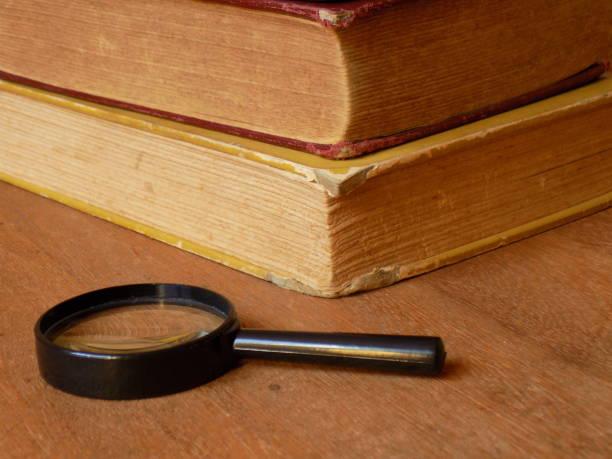 Magnifying Glass with books IV En esta toma la composición muestra el vértice de los libros en dirección a la cámara y la lupa en posición horizontal. libro stock pictures, royalty-free photos & images
