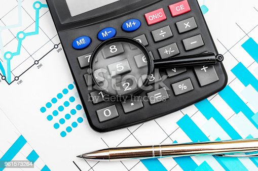 istock Magnifying glass with calculator and pen on the colour business graphs. Top view. Close up. 961573264