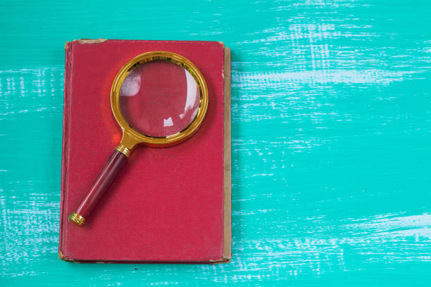Magnifying glass with text book on wood stock photo
