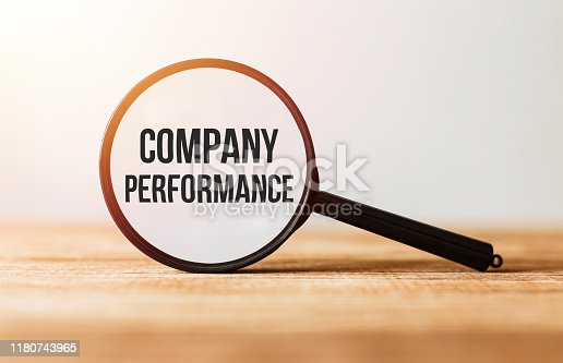 1163501702istockphoto Magnifying glass with text Company Performance on wooden table. 1180743965