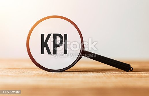 Magnifying glass with text KPI on wooden table.