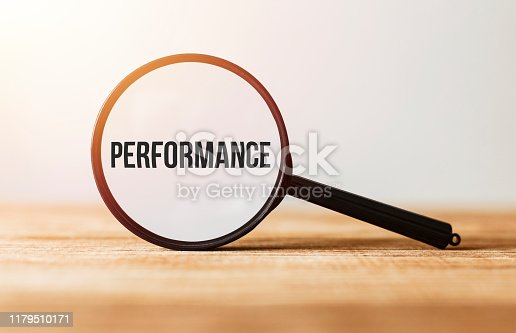 1163501702istockphoto Magnifying glass with text Performance on wooden table. 1179510171