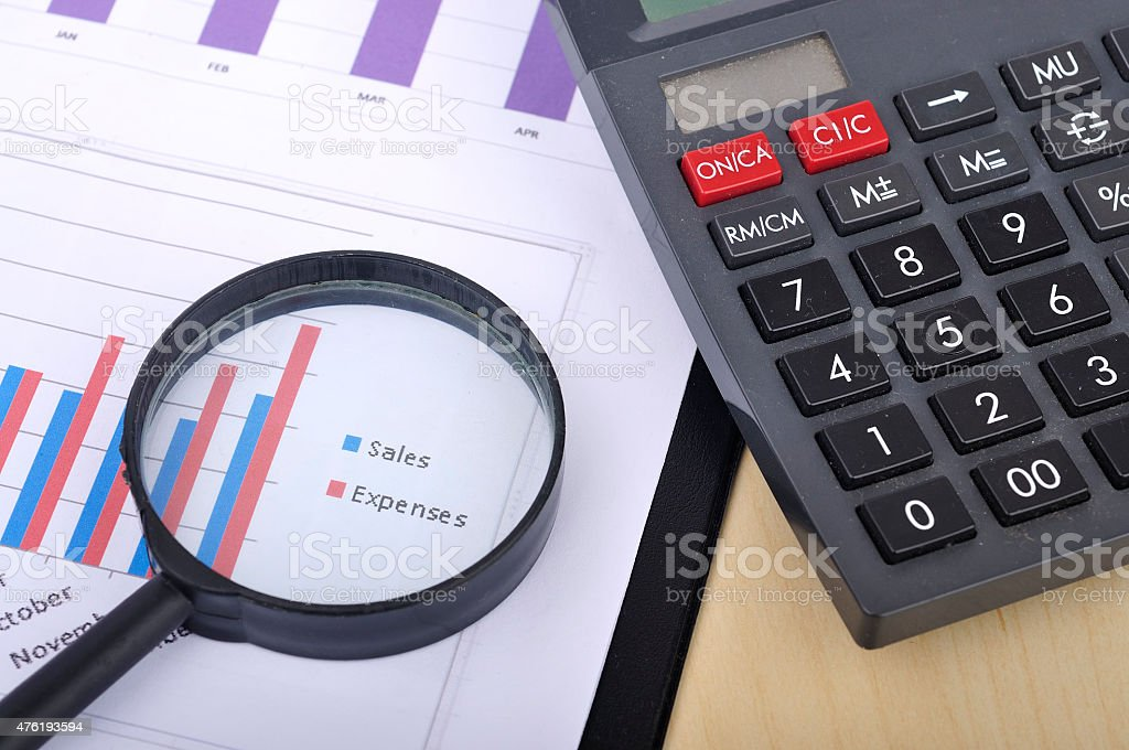 Magnifying Glass With Yearly Graph Bar Representing 'Sales/Expenses' With Calculator stock photo