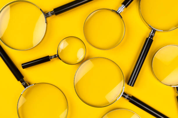 Magnifying Glasses Magnifying glasses on the yellow background. magnifying glass stock pictures, royalty-free photos & images