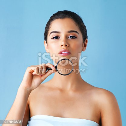 Studio portrait of a beautiful young woman holding a magnifying glass against a blue background