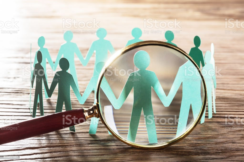 Magnifying The Paper Cut Out Human Figure stock photo