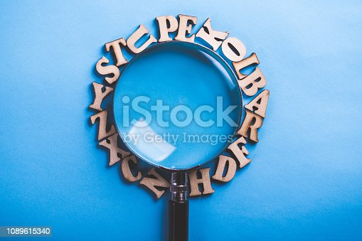 istock Magnifying With Wooden Alphabets Around On Blue Background 1089615340