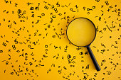 istock Magnifying With Wooden Alphabets Around On Yellow Background 1200976833
