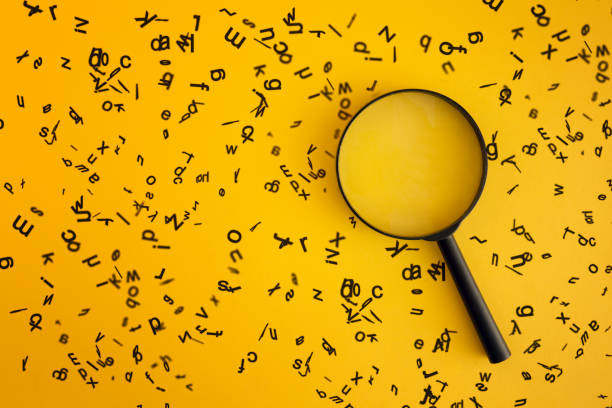 magnifying with wooden alphabets around on yellow background - dictionary stock pictures, royalty-free photos & images