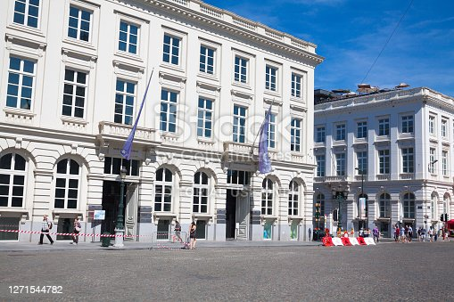 Magritte Museum at Place Royale in Brussels captured in summertime. At facade are flags. Some people are walking in street