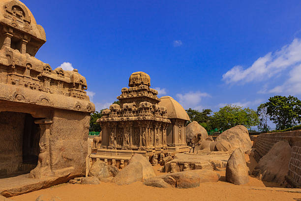 Mahabalipuram, India: 1300 Year Old Pancha Rathas, sculpted in Granite Image shows the Arjuna and Draupadi Rathas of the Pancha Rathas (also known as Pandava Rathas), a monument complex at Mahabalipuram or Mamallapuram, on the Coromandel Coast of the Bay of Bengal, in the state of Tamil Nadu, India. Dating from the late 7th century, it is attributed to the reigns of King Mahendravarman I and his son Narasimhavarman I (630–680 AD) of the Pallava Kingdom. The Arjuna Ratha is the monument in the centre, Nandi, the bull, can be seen to the right. To the left is a section of the Bhima Ratha and behind the Arjuna Ratha, is the Draupadi Ratha.The structures are without any precedence in Indian temple architecture and are carved out of a single granite rock each. Remarkably well preserved for monuments that are over 1300 years old; they withstood the ravages of the Tsunamis of the 13th Century and 2004. They however display the effects of wind and sand erosion of over a thousand three hundred years. These are not temples as they are unfinished, and were never consecrated. They are part of the UNESCO World Heritage site at Mahabalipuram. Photo shot in the afternoon sunlight; horizontal format. chandra dhas, stock pictures, royalty-free photos & images