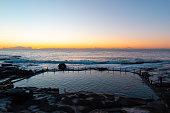 Rocky beach coastline view with clear blue sky.