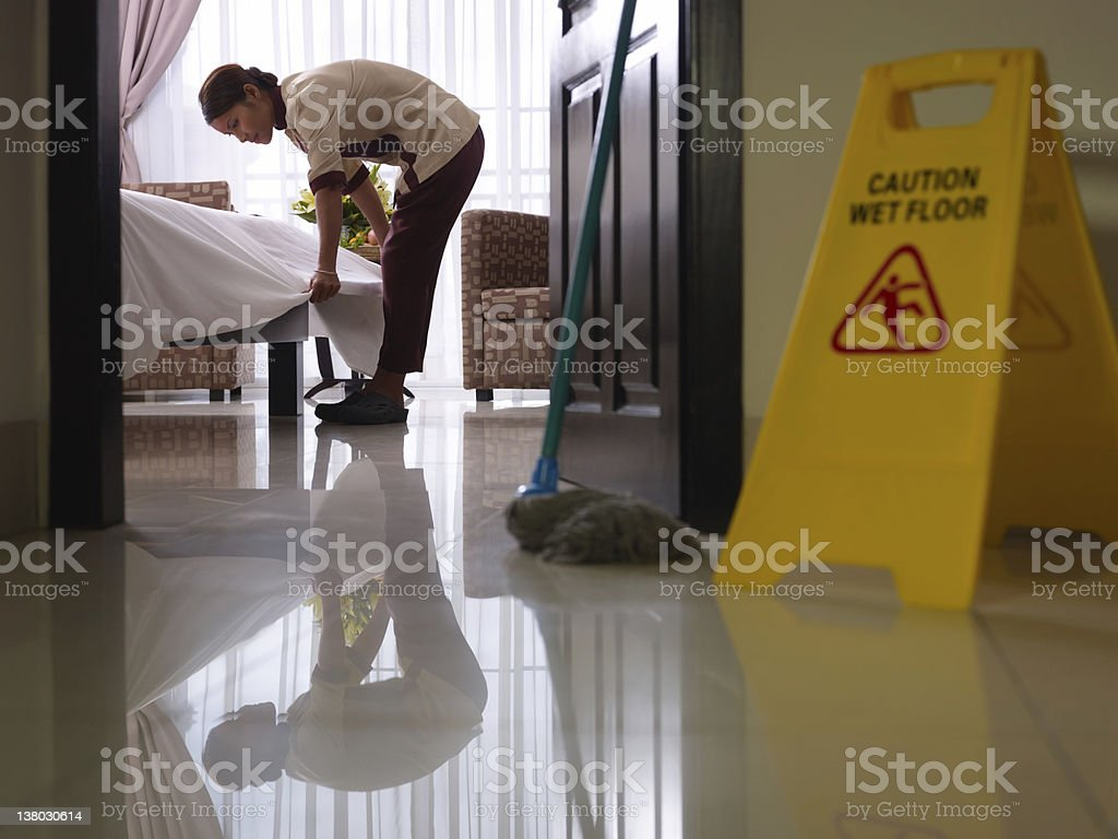 Maid at work and cleaning in luxury hotel room stock photo