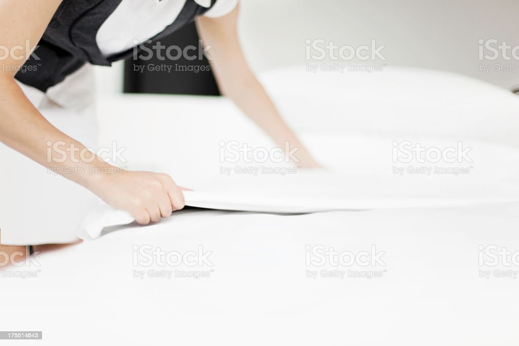 Maid Changing Sheets in a Hotel Room stock photo