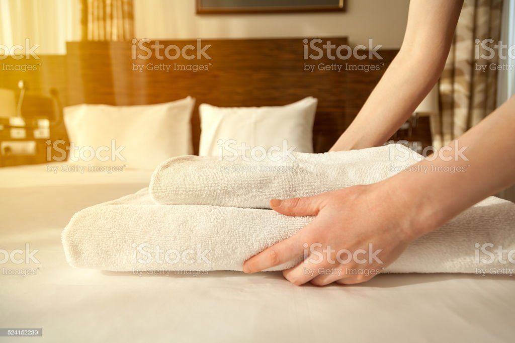 Maid changing towels in hotel room stock photo